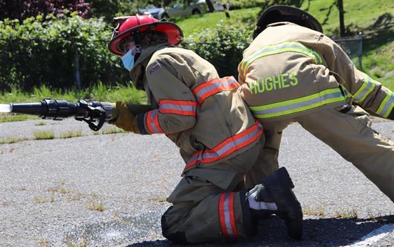 2 students in firefighter gear folding a firehose