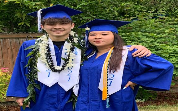 2 smiling graduates in cap and gown